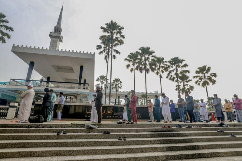 Muslims perform Eid Al-Fitr prayers outside the National Mosque before being told to leave by the police in Kuala Lumpur May 24, 2020 — Picture by Firdaus Latif