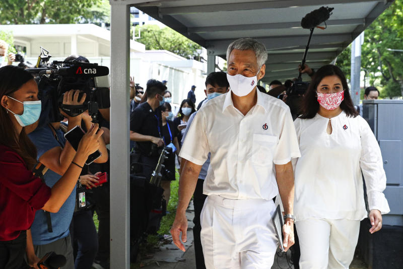 People's Action Party Secretary-General and Singaporean Prime Minister Lee Hsien Loong, center, arrives at a nomination center with his team to submit their nomination papers ahead of the general election in Singapore, Tuesday, June 30, 2020. Campaigning has begun for Singapore's general elections, with the opposition hoping to dent the ruling party's supermajority in parliament with support from Prime Minister Lee's estranged younger brother.  (AP Photo/Yong Teck Lim)