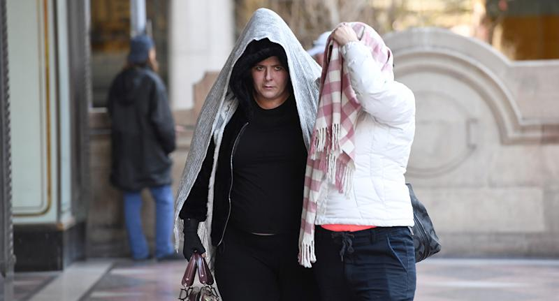 Alison Mains is seen outside Sydney's Downing Centre courthouse while covering her head with a blanket.