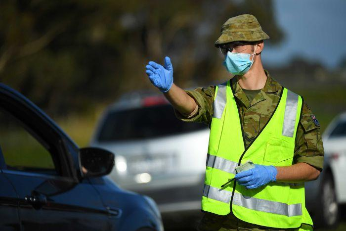 An army officer in a high-vis vest, gloves and a mask directs traffic.