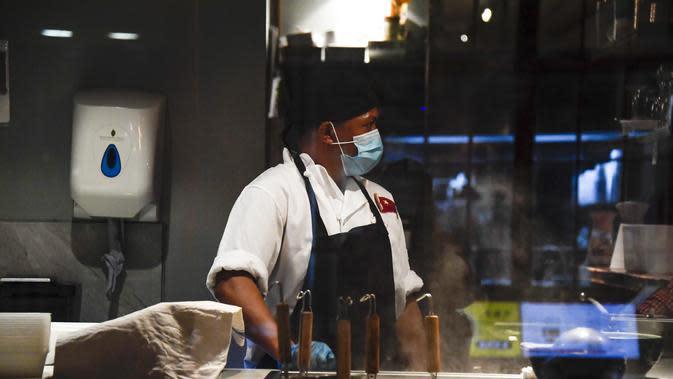 Seorang chef memakai masker pelindung di dapur sebuah restoran di Soho, London, Selasa (22/9/2020). Perdana Menteri Inggris, Boris Johnson, telah mengumumkan bahwa pub dan restoran tutup pada pukul 10 malam, karena lonjakan kasus virus corona di seluruh Inggris. (AP Photo / Alberto Pezzali)