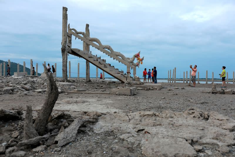 FILE PHOTO: People walk and take pictures at the ruins of a Buddhist temple which has resurfaced in a dried-up dam due to drought, in Lopburi, Thailand
