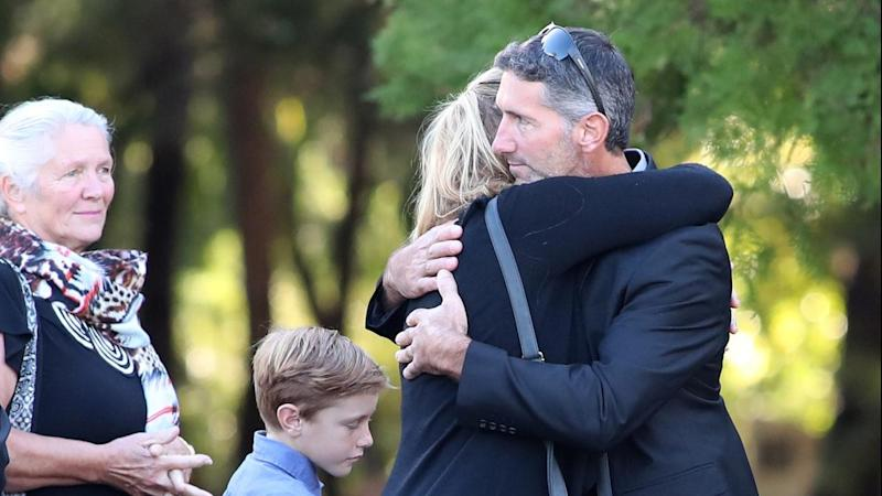 Aaron Cockman embraces a loved one at the funeral of his four children who were killed near Margaret River. Source: AAP