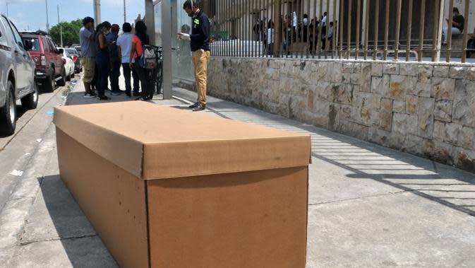 Tampilan kotak kardus yang digunakan sebagai peti mati di sebuah truk di luar pemakaman di Guayaquyil, Ekuador, Senin (6/4/2020). Kehabisan peti mati, kota terbesar di Ekuador yang menjadi klaster wabah virus corona itu terpaksa menggunakan kotak kardus untuk korban Covid-19. (Jose Sanchez/AFP)