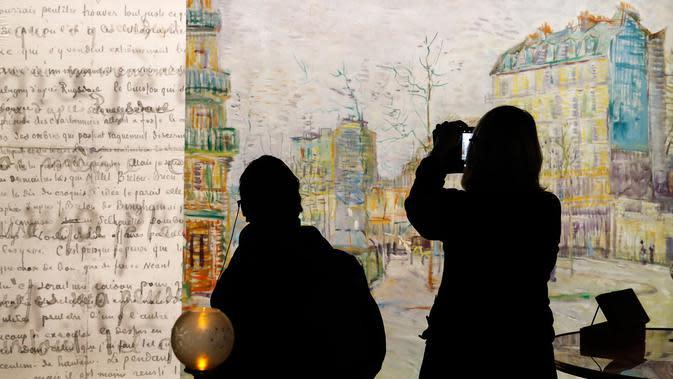 Pengunjung mengamati sebuah koleksi dalam proyek pameran Meet Vincent van Gogh Experience di London, Inggris, Selasa (25/2/2020). Pameran ini mengajak para pengunjung menyelami dunia sang maestro. (Xinhua/Han Yan)