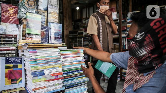 Pedagang menata buku dagangannya di kawasan Kwitang Jakarta, Jumat (26/6/2020). Sejumlah pedagang mengaku penjualan buku mengalami penurunan hingga 50 persen karena imbauan Pemerintah untuk tinggal dirumah dan libur sekolah selama pandemi COVID-19. (Liputan6.com/Faizal Fanani)