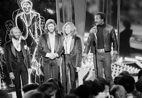 "FILE - In this Dec. 8, 1977, file photo, The Bee Gees, from left, Maurice, Barry and Robin Gibb, join actor Jim Brown, right, on Stage 14 of Paramount Studios during a disco party for the premiere of ""Saturday Night Fever"" in Los Angeles. A representative said on Sunday, May 20, 2012, that Robin Gibb has died at the age of 62. (AP Photo/File)"