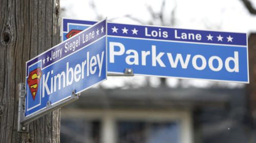 In this Tuesday, April 2, 2013 photo shows street signs where Jerry Siegel lived in the Glenville neighborhood in Cleveland. The Siegel house has become a mini-pilgrimage site for Superman fans and it's easy to pick it out on a street with a mix of renovated and dilapidated homes. (AP Photo/Tony Dejak)