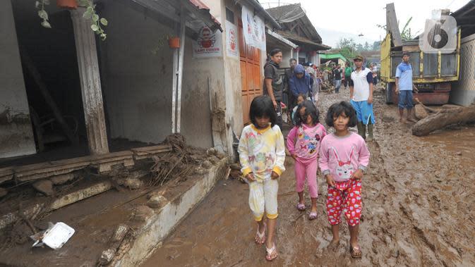 Anak-anak berjalan melintasi lumpur usai banjir bandang melanda Kampung Cibuntu, Desa Pasawahan, Kecamatan Cicurug, Sukabumi, Jawa Barat, Selasa (22/9/2020). Data sementara puluhan bangunan rusak berat, 12 rumah hanyut, dan dua korban hilang masih dicari. (merdeka.com/Arie Basuki)