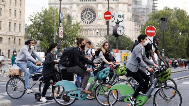 Pengendara sepeda yang mengenakan masker melintas di depan Katedral Notre Dame.