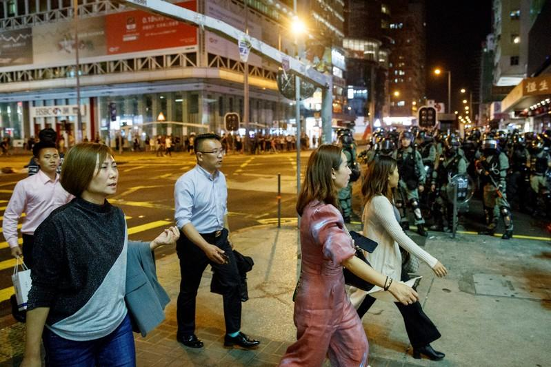 Locals pass police in riot gear during a standoff with protesters in Mong Kok in Hong Kong