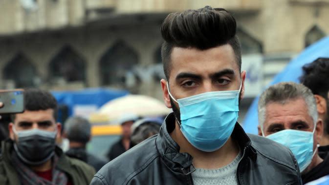 Seorang pria mengenakan masker di sebuah jalan di Baghdad, Irak, (25/2/2020). Irak mengumumkan empat kasus baru COVID-19 di Provinsi Kirkuk, wilayah utara, pada Selasa (25/2), sehingga total pasien terinfeksi di negara itu bertambah menjadi lima orang. (Xinhua/Khalil Dawood)