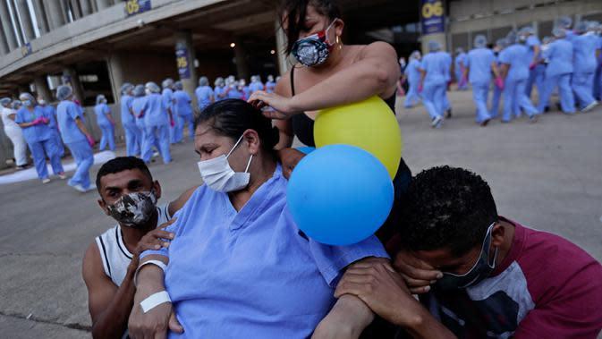 Helena Elvira (63) menerima pelukan dari anak-anaknya saat keluar dari rumah sakit di Stadion Nasional Mane Garrincha di Brasilia, Brasil, Kamis (15/10/2020). Rumah sakita darurat tersebut memulangkan tiga pasien COVID-19 terakhir setelah dinyatakan sembuh (AP Photo/Eraldo Peres)