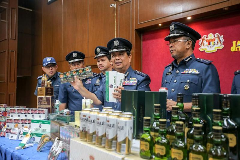 Perak Customs director Mohamad Sarpin poses with seized contraband cigarettes and alcohol worth over RM2 million during a press conference in Ipoh February 25, 2020. — Picture by Farhan Najib