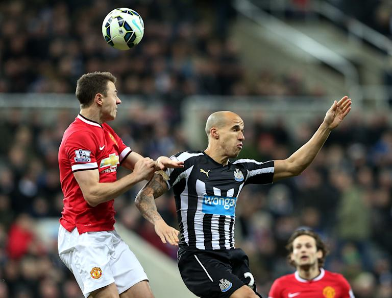 Manchester United's  Jonny Evans, left, vies for the ball with Newcastle United's Gabriel Obertan, right, during their English Premier League soccer match between Newcastle United and Manchester United at St James' Park, Newcastle, England, Wednesday, March, 4, 2015. (AP Photo/Scott Heppell)