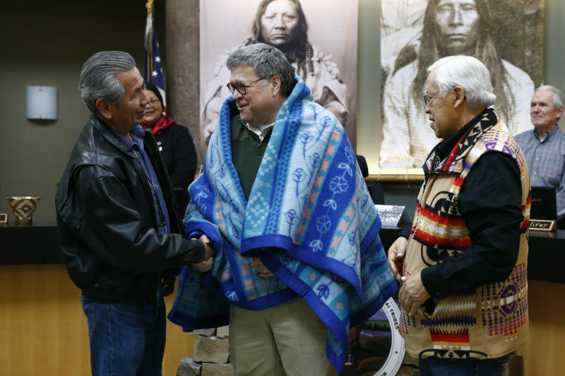 Attorney General William Barr, center, shakes hands with Vernon Finley, left, and Tony Incashola, right, after they presented him with a blanket during a Confederated Salish and Kootenai Tribes council meeting, Friday, Nov. 22, 2019, on the Flathead Reservation in Pablo, Mont. (AP Photo/Patrick Semansky)