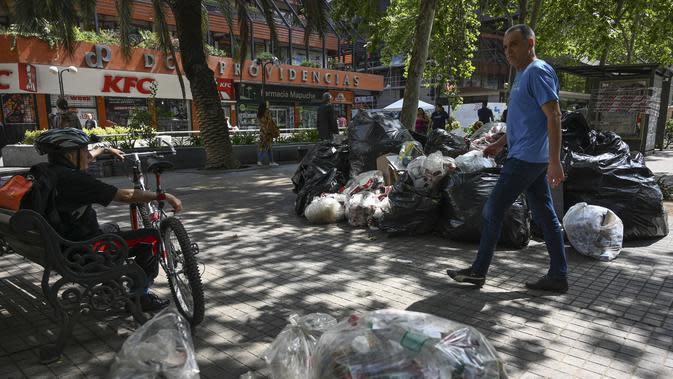 Seorang pria berjalan melewati tumpukan sampah akibat pemogokan petugas sampah di Santiago (14/11/2019). Protes kekerasan meletus di ibukota Chile, Santiago, pada Selasa ketika mata uang negara itu turun ke level terendah dalam sejarah. (AFP/Javier Torres)