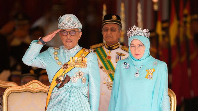 Raja Malaysia Sultan Abdullah Sultan Ahmad Shah (kiri) memberi hormat di samping Ratu Tunku Azizah Aminah Maimunah dan PM Mahathir Mohamad saat upacara pelantikannya di Istana Nasional, Kuala Lumpur, Malaysia, Kamis (31/1). (AP Photo/Yam G-Jun)