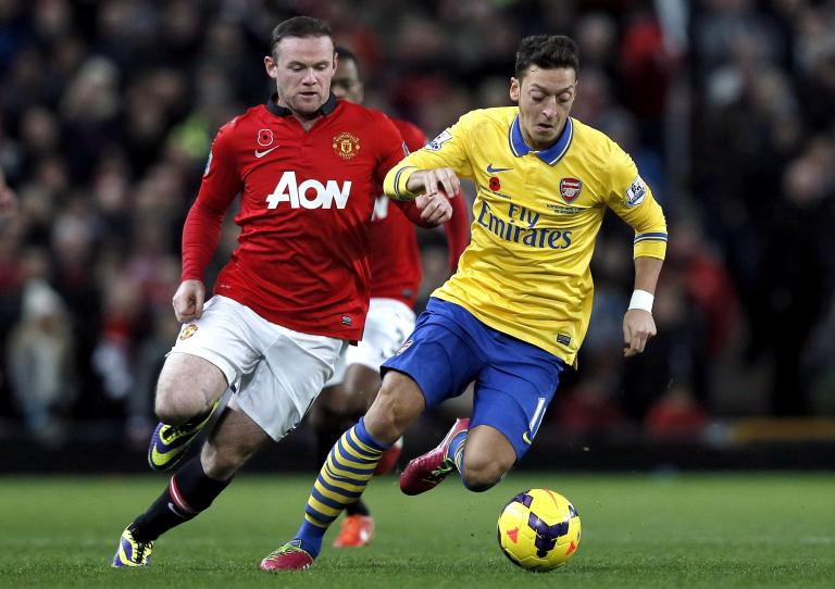 Manchester United's Rooney chases Arsenal's Ozil during their English Premier League soccer match in Manchester