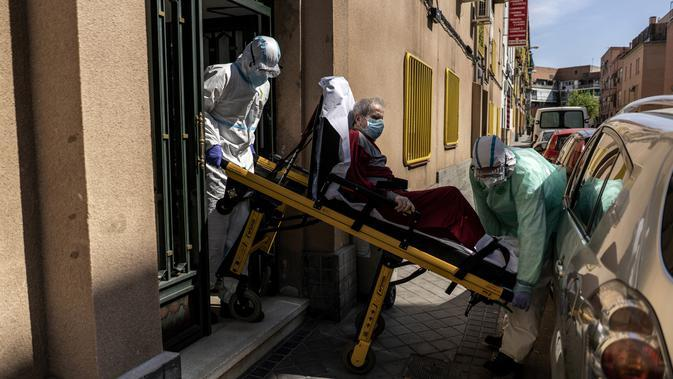 Enrique (92) dibawa oleh petugas medis ke ambulans setelah menunjukkan gejala terinfeksi virus corona COVID-19 di Madrid, Spanyol, Minggu (12/4/2020). Hingga Selasa (14/4/2020) pukul 10.29 WIB, Johns Hopkins University mencatatkan 449.949 pasein COVID-19 dinyatakan sembuh. (AP Photo/Olmo Calvo)