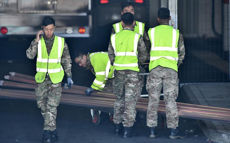 Soldiers help to unload equipment at the new NHS Nightingale hospital in London - Glyn Kirk/AFP