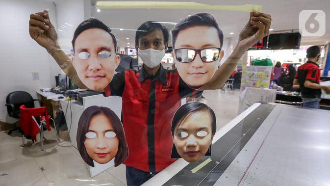 Karyawan menunjukkan hasil cetak pelindung wajah atau face shield karakter di percetakan Bintang Sempurna, Bendungan Hilir, Jakarta, Selasa (23/6/2020). Face shield karakter yang dibuat dari bahan mika PCA anti fog bisa dicuci berulang kali. (Liputan6.com/Fery Pradolo)