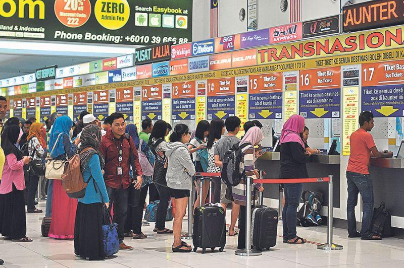 People queue up for bus tickets at the TBS Integrated Terminal in Bandar Tasik Selatan. ― Malay Mail pic