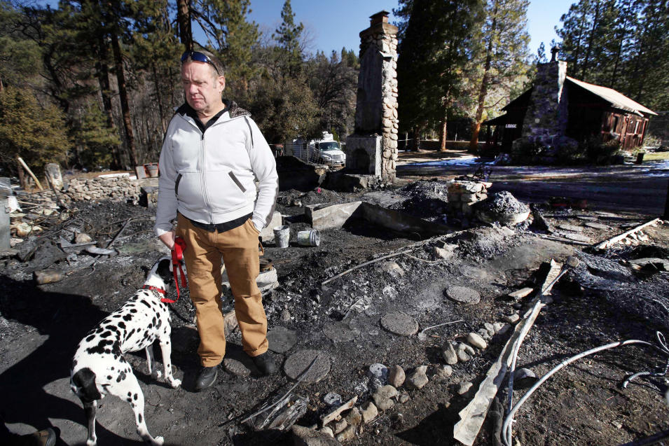 FILE - In this Friday, Feb. 15, 2013 file photo, Rick Heltebrake, with his dog Suni, looks over the burned-out cabin where Christopher Dorner's remains were found after a police standoff Tuesday near Big Bear, Calif. Dorner took his pickup during his escape attempt. Heltebrake, a ranger who takes care of a Boy Scout camp, was checking the perimeter of the camp for anything out of the ordinary when he saw Dorner emerge from behind some trees. (AP Photo/Nick Ut, FIle)