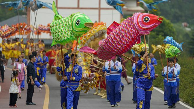 Warga desa mengenakan kostum tradisional ambil bagian dalam sebuah pawai di Distrik Tongliang di Chongqing, China (19/9/2020). Pertunjukan tari naga dan kegiatan rakyat lainnya digelar untuk merayakan festival panen petani China yang jatuh pada Equinox Musim Gugur setiap tahunnya. (Xinhua/Liu Chan)