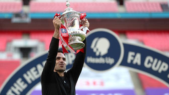 Pelatih Arsenal, Mikel Arteta mengangkat trofi Piala FA setelah mengalahkan Chelsea pada pertandingan final Piala FA di stadion Wembley, London, Minggu (2/8/2020) dini hari. Arsenal juara Piala FA setelah menang dengan skor 2-1. (Catherine Ivill/Pool via AP)