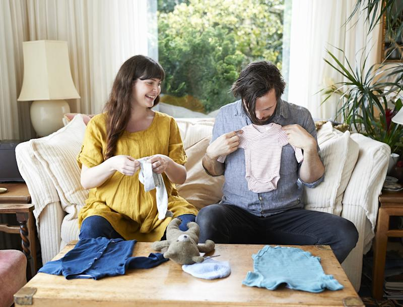 A pregnant couple sit in the living room of their home and look at baby clothes.