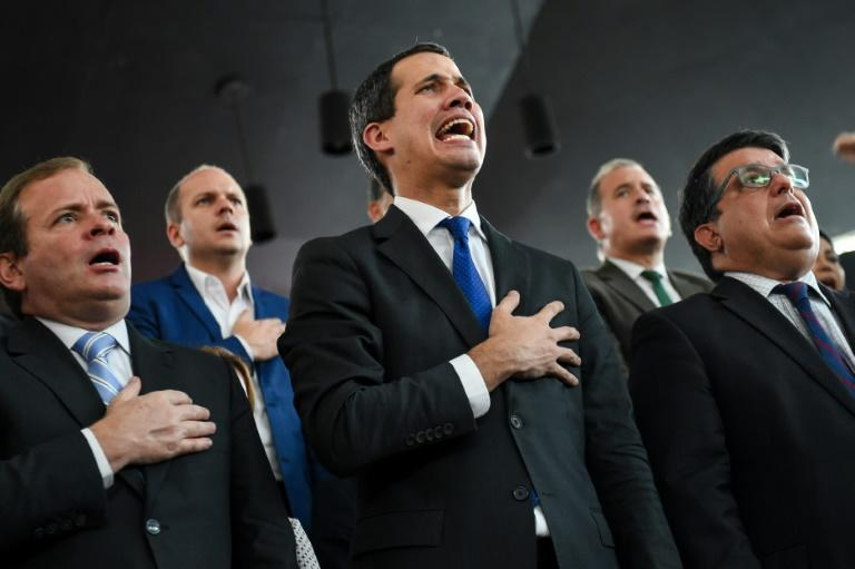 Venezuelan opposition leader Juan Guaido (C) sings the national anthem, accompanied by opposition lawmakers and supporters, during a press conference at a theater in Caracas, after a standoff over his position as National Assembly speaker