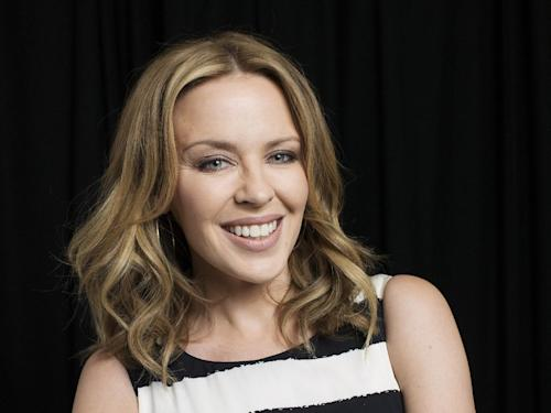 """In this June 19, 2013 photo, Australian recording artist Kylie Minogue poses for a portrait in New York. The singer compiled a book looking back at her fashion choices, particularly her stage costumes, in a new book called """"Kylie Fashion,"""" published by Running Press. (Photo by Victoria Will/Invision/AP)"""