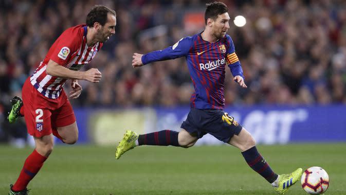 Striker Barcelona, Lionel Messi, berusaha melewati bek Atletico Madrid, Diego Godin, pada laga La Liga di Stadion Camp Nou, Sabtu (6/4). Barcelona menang 2-0 atas Atletico Madrid. (AP/Manu Fernandez)
