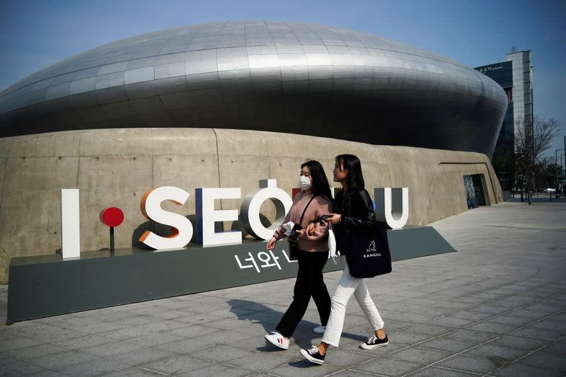 FILE PHOTO: Women wearing masks to protect against contracting the coronavirus disease (COVID-19) walk along a street in Seoul, South Korea