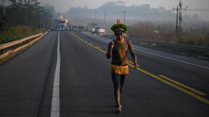 Masyarakat suku Kayapo membawa tongkat saat memblokir jalan raya utama Trans-Amazonian di Negara Bagian Para, Brasil (17/8/2020). (AFP Photo/Carl De Souza)