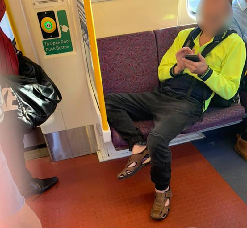 A man in high visibility uniform is lying across two seats in a train carriage, accused of refusing to move over for a pregnant woman. .