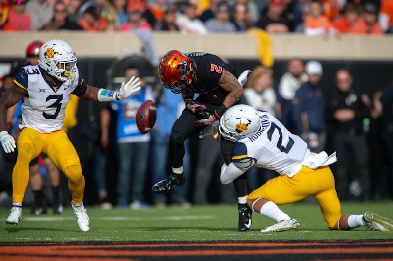 STILLWATER, OK - NOVEMBER 17: West Virginia Mountaineers safety Kenny Robinson Jr. (2) hits Oklahoma State Cowboys wide receiver Tylan Wallace (2) causing a fumble during the Big 12 college football game on November 17, 2018 at Boone Pickens Stadium in Stillwater, Oklahoma. (Photo by William Purnell/Icon Sportswire via Getty Images)