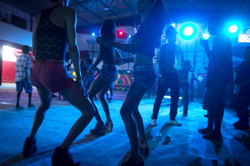 "In this Dec. 8, 2012 photo, people dance during a funk ""baile,"" or party, in a slum in western Rio de Janeiro, Brazil. A 2007 law that had made it virtually impossible to hold the traditional open-air funk parties in favelas was repealed in 2009, and the musical genre was recognized as a ""cultural movement."" Dance face-offs between performers of ""passinho,"" a type of break dancing associated with Rio's funk scene, now come with corporate sponsorship. (AP Photo/Felipe Dana)"