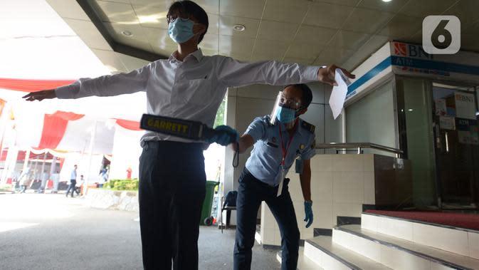 Petugas memeriksa peserta yang akan mengikuti Seleksi Kompetensi Bidang (SKB) berbasis Computer Assisted Test (CAT) untuk Calon Pegawai Negeri Sipil (CPNS) Kemenkumham di Gedung Kepegawaian Negara, Jakarta, Rabu (2/9/2020). (merdeka.com/Imam Buhori)
