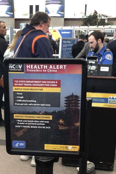 FILE - In this March 2, 2020 file photo, a health alert for people traveling to China is shown at a TSA security checkpoint at the Denver International Airport in Denver. The spread of the coronavirus, including cases in the U.S., has many small business owners canceling or changing plans, arranging for staffers to work from home, even asking employees who have traveled to places with widespread outbreaks to stay home for as long as a month.  (AP Photo/Charles Rex Arbogast)
