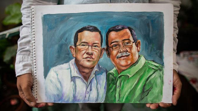 Pelukis Nikaragua Fernando Torres, 28, memegang lukisan saudara laki-laki Adan Augusto Alonso (kiri) dan Maximo Guillerno Alonso (kanan), dokter medis yang meninggal akibat COVID-19 yang terjangkit saat memberikan bantuan kepada orang lain di Managua pada 21 Juni 2020. (INTI OCON/AFP)