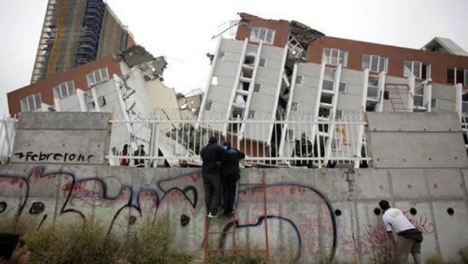 Orang-orang melihat bangunan yang runtuh di Concepcion, Chili, Minggu, 28 Februari 2010. Gempa berkekuatan 8,8 melanda Chili pada Sabtu pagi. (AP Photo/Natacha Pisarenko)