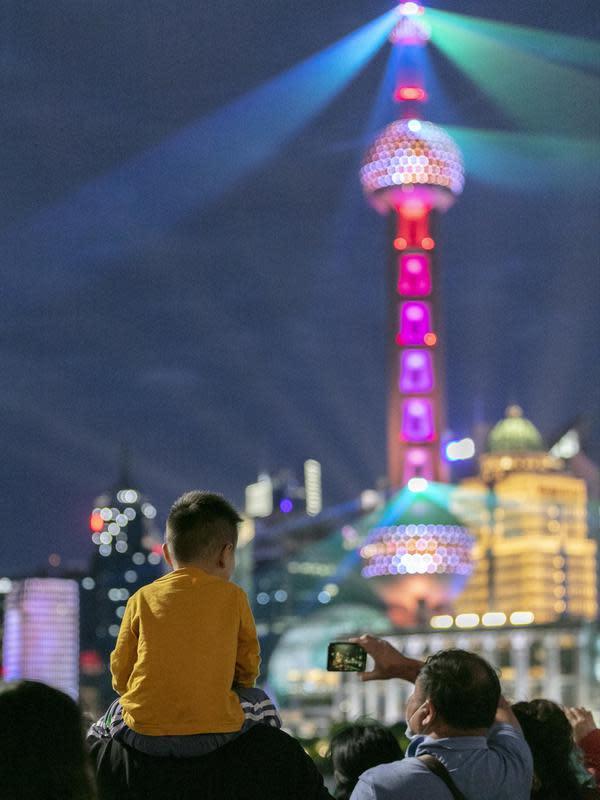 Orang-orang menikmati pertunjukan cahaya di Bund, Shanghai, China timur, pada 5 Oktober 2020, hari kelima libur Hari Nasional dan Festival Pertengahan Musim Gugur. (Xinhua/Wang Xiang)