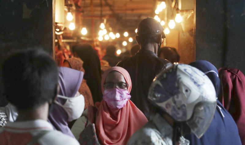 Muslim women wear face masks as they shop in preparation of the upcoming Eid al-Fitr holiday that marks the end of the holy fasting month of Ramadan amid fears of the new coronavirus outbreak at a market in Jakarta, Indonesia, Friday, May 22, 2020. (AP Photo/Achmad Ibrahim)
