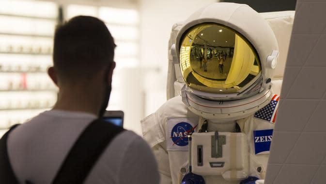 Seorang pelanggan yang mengenakan masker mengabadikan foto pakaian luar angkasa di CF Toronto Eaton Center, Toronto, Kanada, 6 Oktober 2020. Hingga Selasa (6/10/2020) sore waktu setempat, Kanada melaporkan 170.945 kasus COVID-19 termasuk 9.527 kematian. (Xinhua/Zou Zheng)