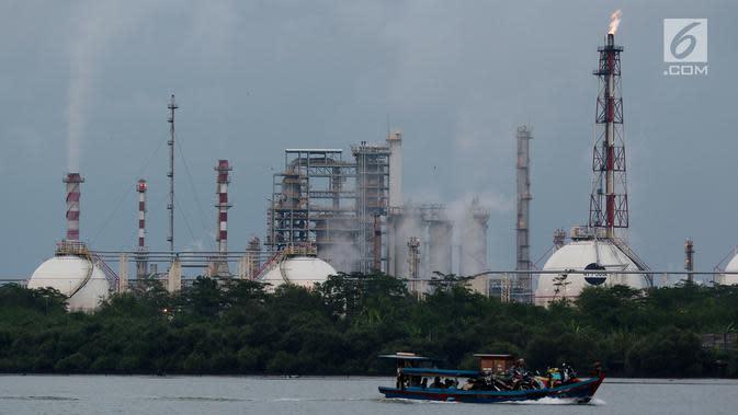 Perahu kayu membawa muatan melintas di dekat kilang minyak Pertamina Refenery Unit IV Cilacap, Rabu (7/2). RU IV Cilacap menjadi kilang dengan kapasitas terbesar di Indonesia. (Liputan6.com/JohanTallo)