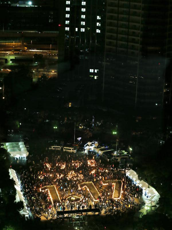 Penduduk Kobe berkumpul di sekitar lilin yang bertuliskan