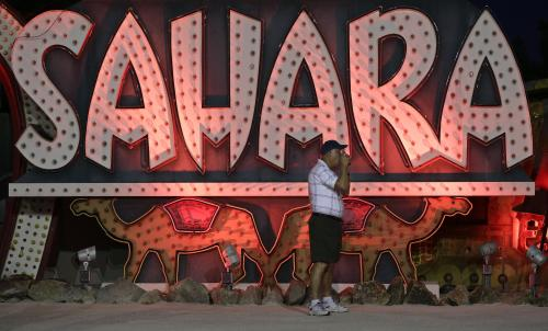 A tourist takes a photo while visiting at the Neon Museum in Las Vegas on Friday, May 24, 2013. For the past six months, tourists have had to squint up at the hulking metal forms through the desert sun. On Friday, the Neon Museum unveiled nighttime hours. (AP Photo/Julie Jacobson)