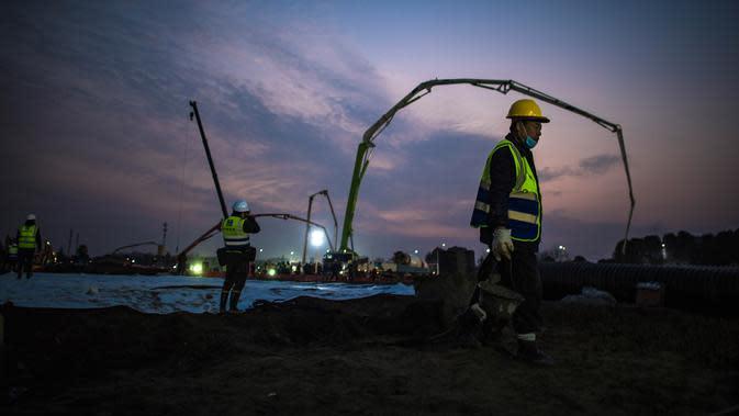 Gambar pada 28 Januari 2020, pekerja konstruksi di lokasi Rumah Sakit Huoshenshan yang sedang dibangun di Wuhan di Provinsi Hubei, China. Rumah sakit khusus pasien virus Corona yang berkapasitas 1.000 tempat tidur itu ditargetkan bisa digunakan pada 3 Februari mendatang. (Xiao Yijiu/Xinhua via AP)
